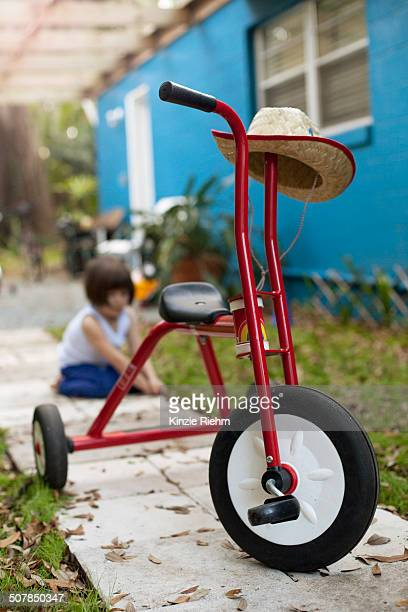 Tricycle in front of four year old girl on garden path