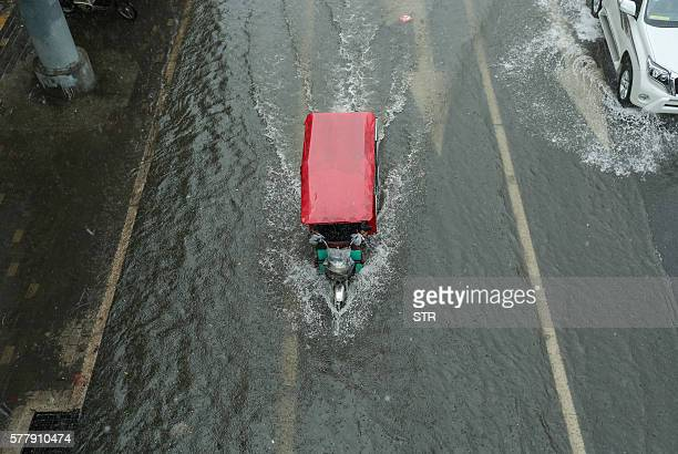 TOPSHOT A tricycle makes its way along a flooded street in Beijing on July 20 2016 Some areas and streets in Beijing have started to flood over due...
