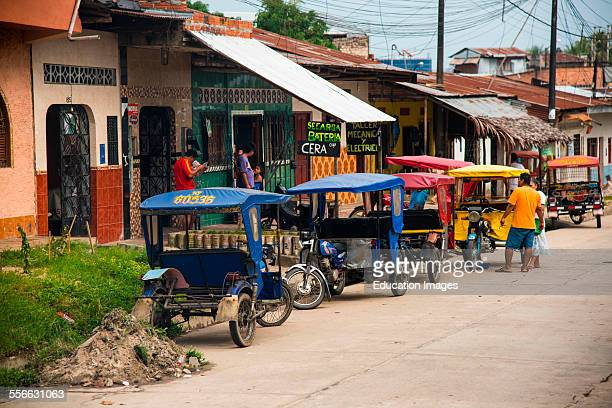 Tricycle motor taxis line street in Iquitos Peru