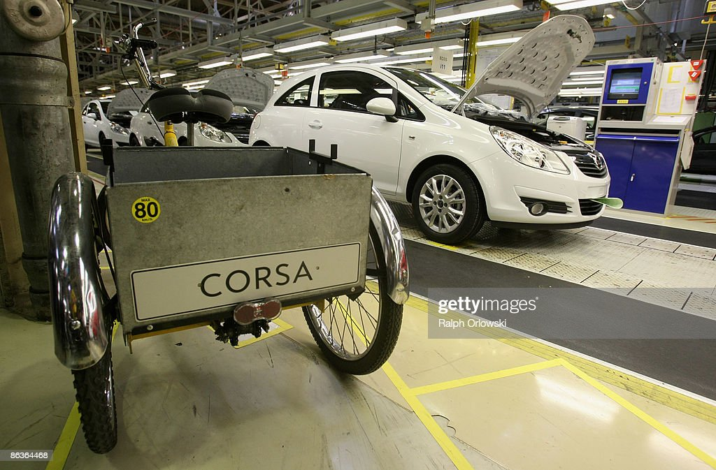A tricycle stands next to an Opel Corsa at a plant on May 4, 2009 in Eisenach, Germany. Representatives of the German government, officials of car manufacturer Opel and managers of Italian carmaker Fiat will meet today in Berlin to discuss a merger between Fiat, Opel and U.S. carmaker Chrysler.