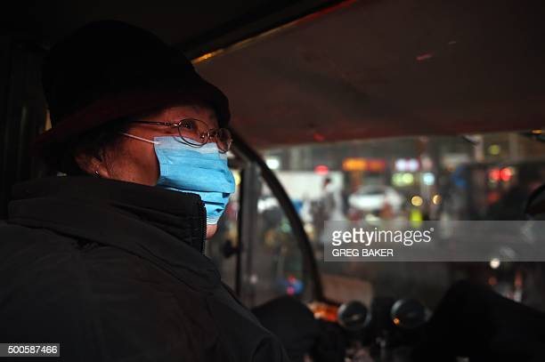 A tricycle taxi driver wears a mask as she waits for customers on a polluted day in Beijing on December 9 2015 Pollution red alerts spread to more...