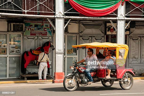 Tricycle taxi passes man and model horse Iquitos Peru