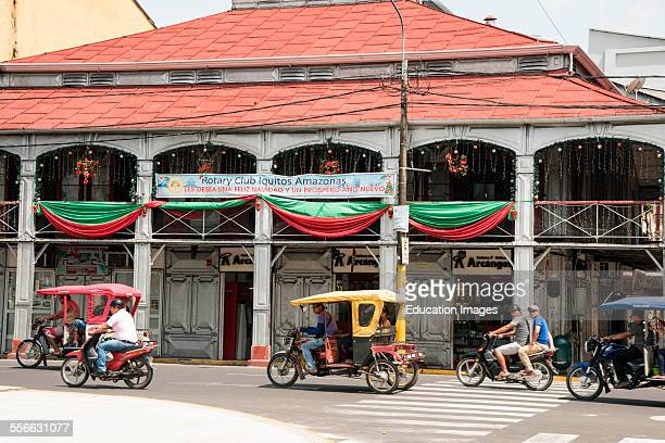 Tricycle taxis on street in front of Iron Building Iquitos Peru