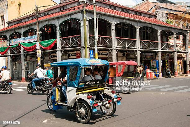 Tricycle taxis on street in front of Iron Building Iquitos Peru Reputed to be designed by Gustave Eiffel