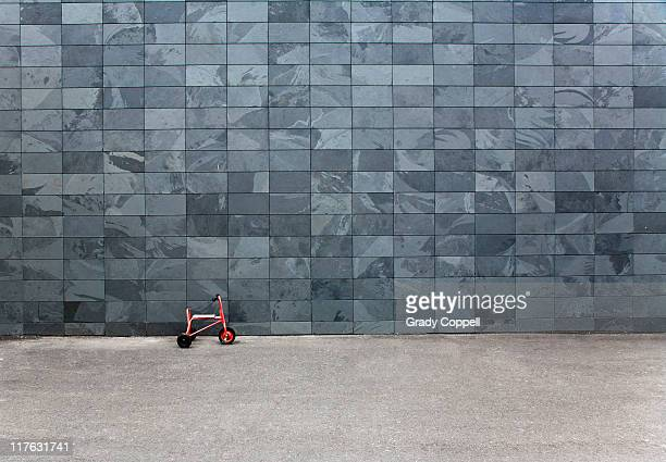 Tricyle in front of large slate wall