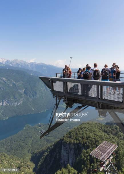 Triglav National Park Upper Carniola Slovenia Visitors on the observation deck at the Vogel Ski Centre taking photographs Lake Bohinj below