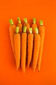 Trimmed carrots on an orange background
