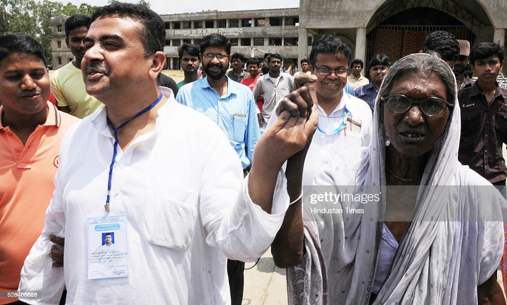 Trinamool Congress strongman and candidate from Nandigram Suvendu Adhikari holding hands with Narmada Sit, one of the leading faces during anti land acquisition movement in 2007 at Sonachura Bazar on May 5, 2016 in Nandigram, India. Over 84 per cent of the electorate exercised their franchise in the sixth and last phase of Assembly election in West Bengal. 25 assembly seats, including 16 in Purba Medinipur and nine in Coochbehar districts, are going to polls. Over 58 lakh voters will decide political fate of 170 candidates, including 18 women.