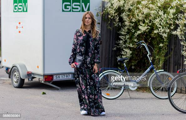 Trine Kjaer wearing a dress with floral print and a Loewe clutch outside Ganni during the second day of the Copenhagen Fashion Week Spring/Summer...