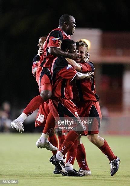 Trinidad and Tobago's Stern John jumps on Emery John and Densill Theobald after a goal by teammate Christopher Birchall against Honduras during Round...