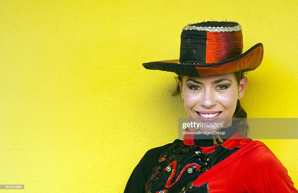 Trinidad Cuba dancer in costume and hat against yellow wall and smile.