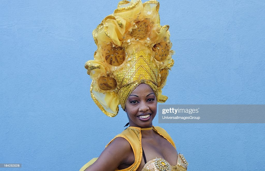 Trinidad Cuba dancer in show costume gold against blue wall and colorful head dress and smile.