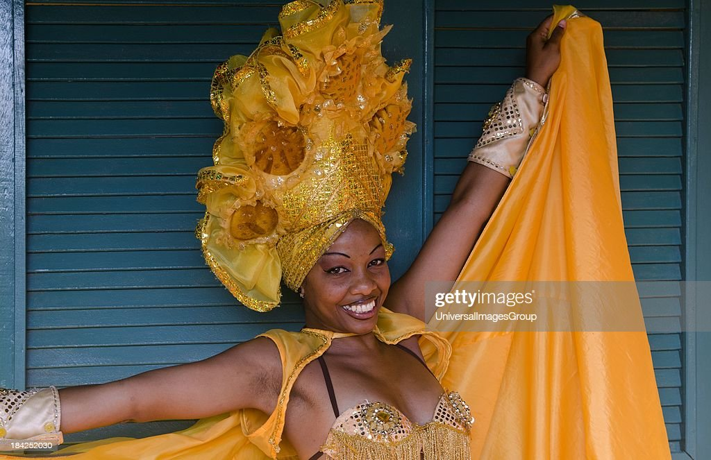 Trinidad Cuba dancer in show costume gold against green door and colorful head dress and smile.
