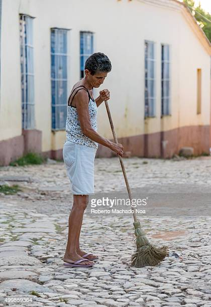 Trinidad de Cuba scenes Lady sweeping cobbled street with a long broom Trinidad village is very clean and neat and is a UNESCO World Heritage Site...