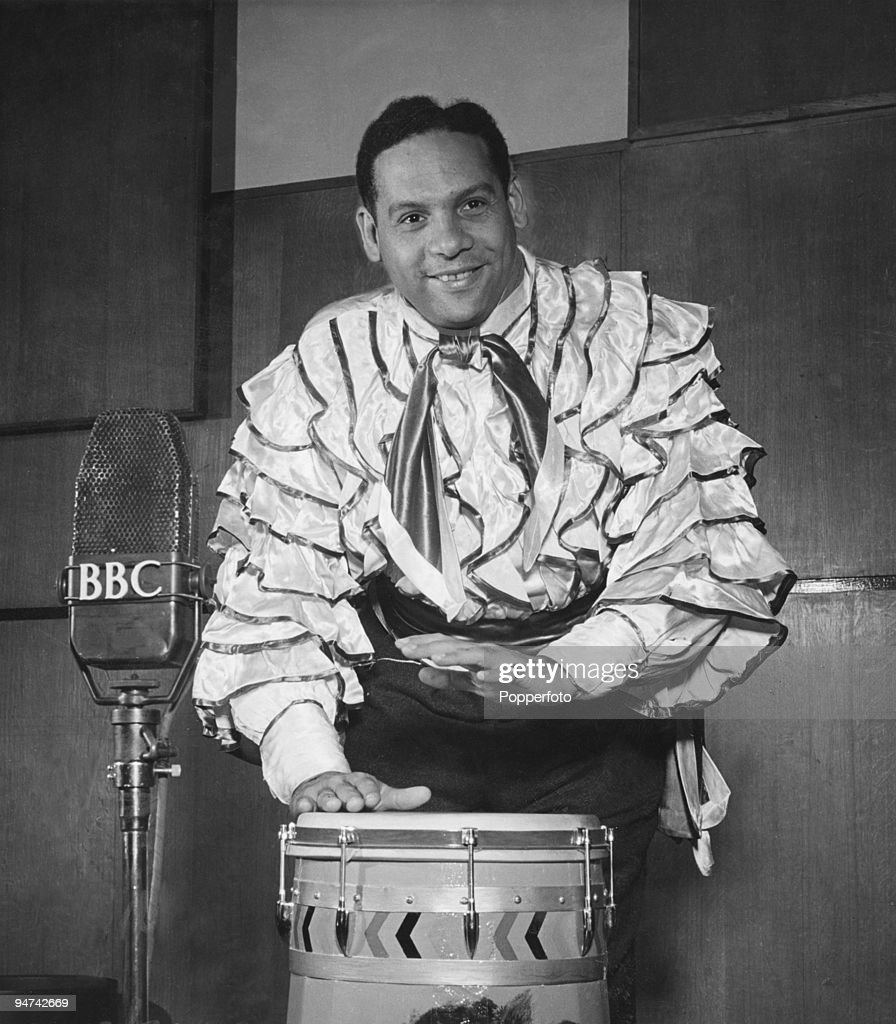 Trinidadian singer and bandleader Edmundo Ros performing in a BBC radio studio, London, 7th October 1949.