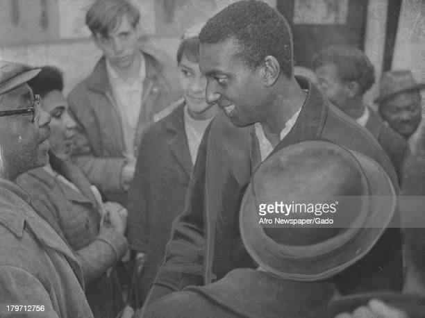 Trinidadianborn American Civil Rights activist Stokely Carmichael is shaking a man's hand as a crowd of people are gathered around them New Haven...