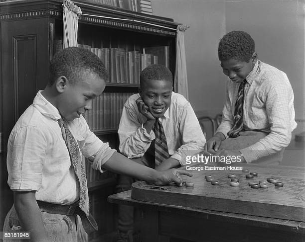 A trio of boys playing a game of Crokinole on a table top at the Colored Boys Club in Harlem New York 1934