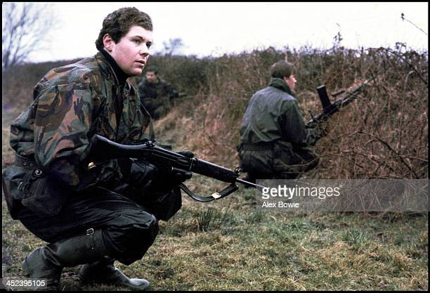 A trio of British soldiers take cover behind a hedgerow during a patrol in County Fermanagh along the border separating Northern Ireland and the...