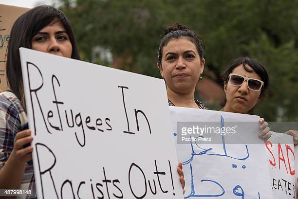 A trio of demonstrators hold signs in English and in Arabic at the rally A collection of activists featuring members on MENA Solidarity Network...
