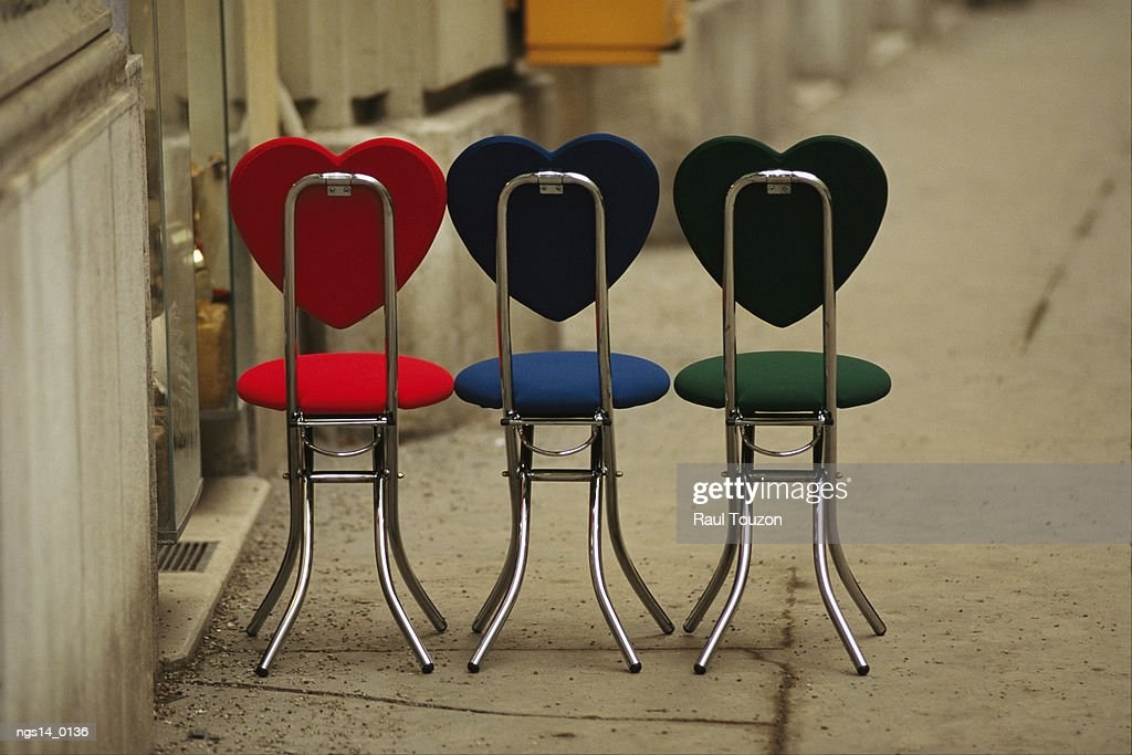 A trio of fashionable chairs with heart-shaped backs on a sidewalk. : Stock Photo