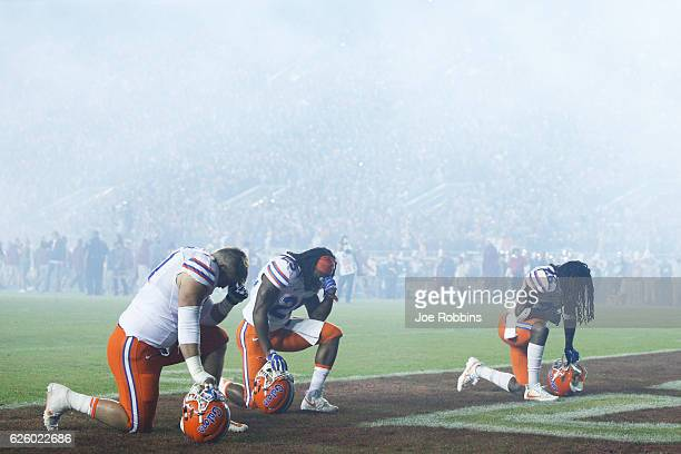 A trio of Florida Gators players kneel to pray before the game against the Florida State Seminoles at Doak Campbell Stadium on November 26 2016 in...
