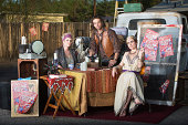 Three serious fortune tellers sitting outside at kiosk