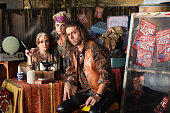 Three serious fortune tellers sitting outside with table