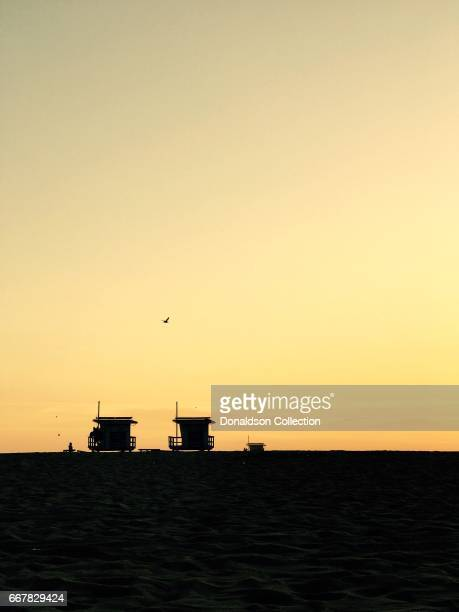 A trio of lifeguard towers silhouetted at sunset on Aoril 1 2017 in Venice Beach California