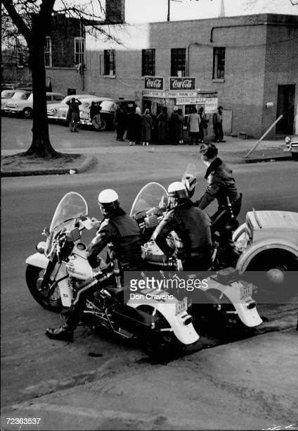 Trio of motorcycle police watching small group of African Americans who are waiting for car pool rides during the Montgomery bus boycott