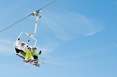 Happy skiers on ski lift - space for text