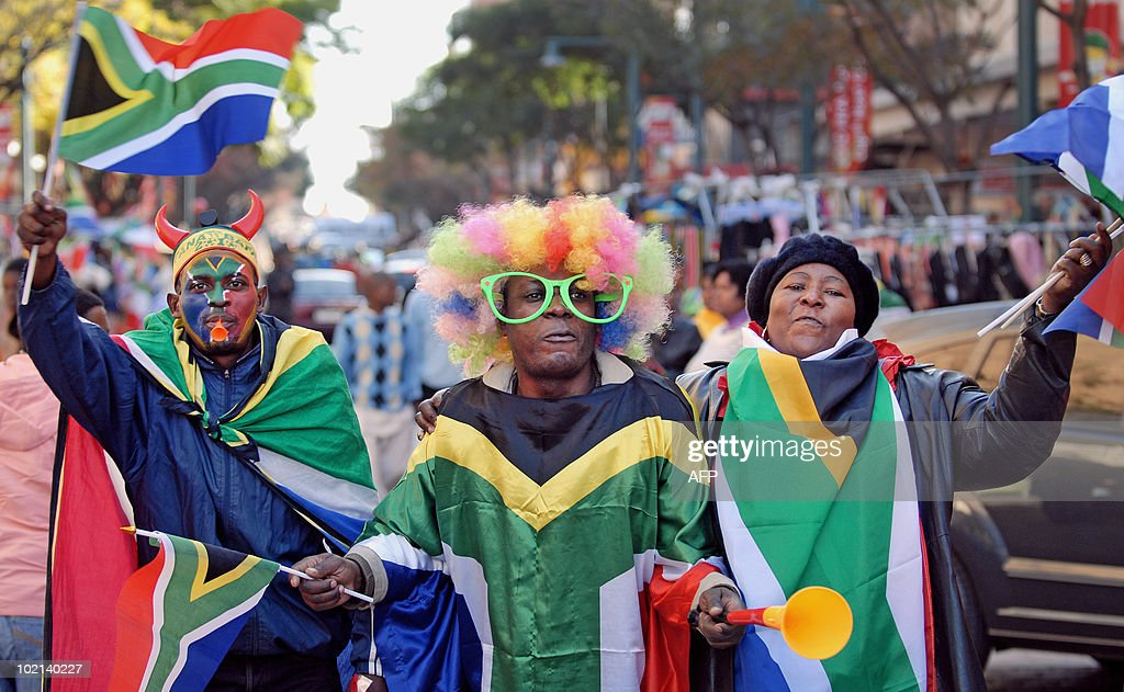 A trio of South African roadside vendors wearing various costumes and the country's flag try to attract customers along a street in Pretoria on June 16, 2010 just hours before the 2010 World Cup football match between South Africa and Uruguay in the city. AFP PHOTO / Monirul Bhuiyan