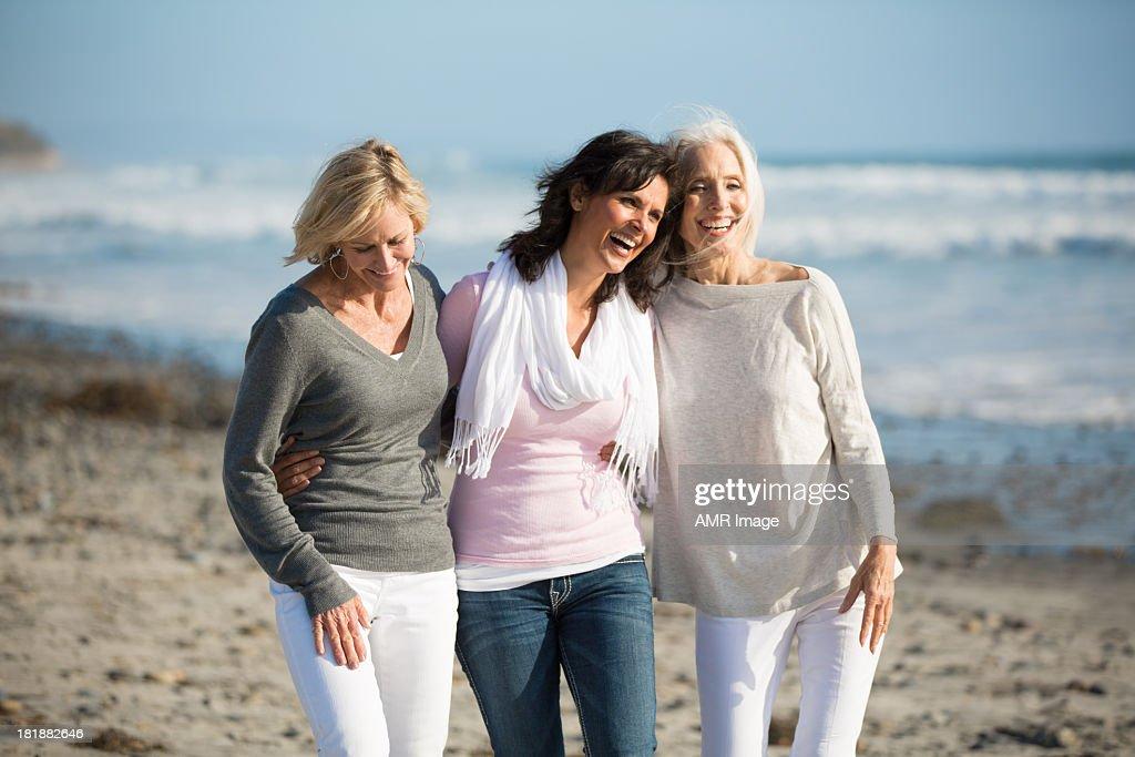 Trio de mulheres, andar na praia : Foto de stock