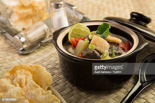 Tripe Broth In Porcelain Pot Placed On Woven Wicker Mat