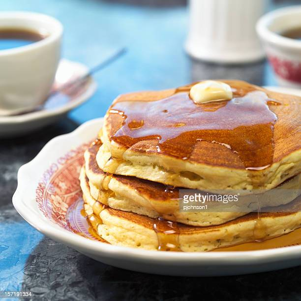 Triple stack of pancakes and maple syrup and coffee