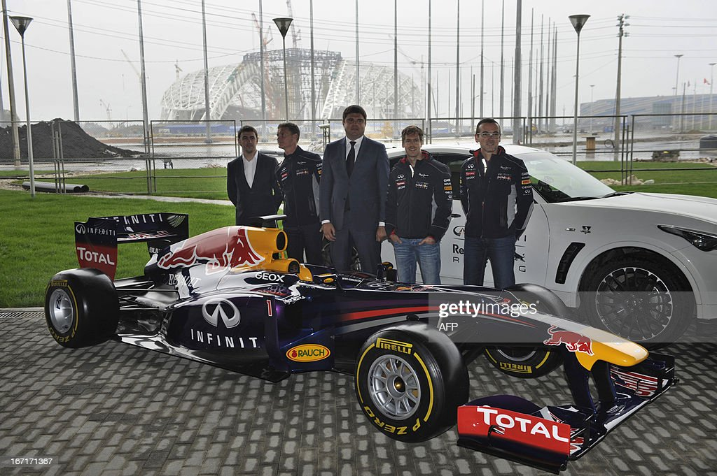 Triple World Formula 1 Champion, Red Bull Racing's German driver Sebastian Vettel (2nd R), ex-Formula 1 driver turned commentator David Coulthard (2nd L) pose fore photo near a racing car in the Black Sea resort of Sochi on April 22, 2013, with Krasnodar region deputy governor Mikhail Buturlakin (C) attending. Vettel and Coulthard attended today a special promotional event at the new Russian Grand Prix circuit in Sochi, the location for the 2014 Winter Olympic. AFP PHOTO / MIKHAIL MORDASOV