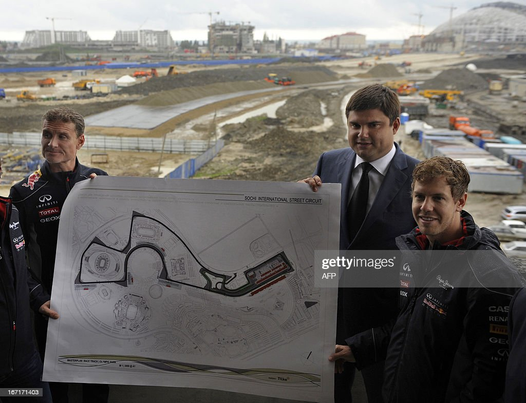 Triple World Formula 1 Champion, Red Bull Racing's German driver Sebastian Vettel (R), ex-Formula 1 driver turned commentator David Coulthard (L) pose fore photo with a map of Russian Grand Prix circuit in the Black Sea resort of Sochi on April 22, 2013, with Krasnodar region deputy governor Mikhail Buturlakin (C) attending. Vettel and Coulthard attended today a special promotional event at the new Russian Grand Prix circuit in Sochi, the location for the 2014 Winter Olympic. AFP PHOTO / MIKHAIL MORDASOV