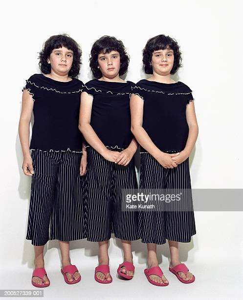 Triplet sisters (6-7) standing in row by wall, portrait