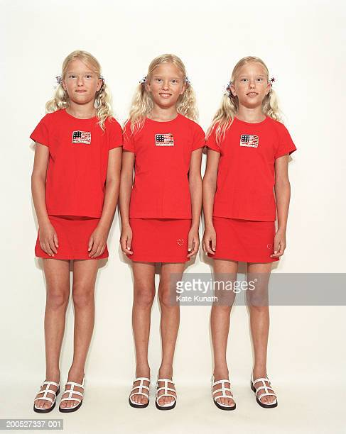 Triplet sisters (6-7) standing in row by wall, smiling, portrait
