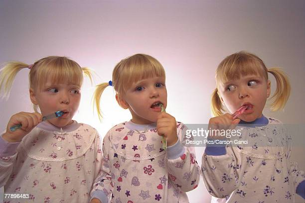 Triplets brushing teeth