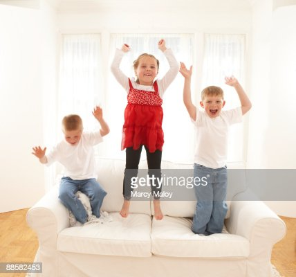 Triplets jumping on a white couch. : Stock Photo