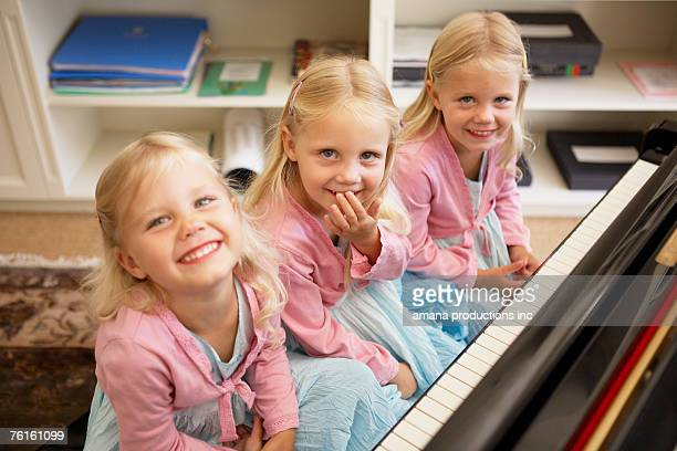Triplets playing piano (high angle view)