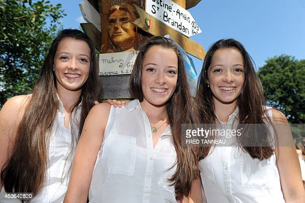 Triplets pose in the Fete des Jumeaux a gathering of twins triplets and quadruplets in Pleucadeuc on August 15 2014 AFP PHOTO/ FRED TANNEAU