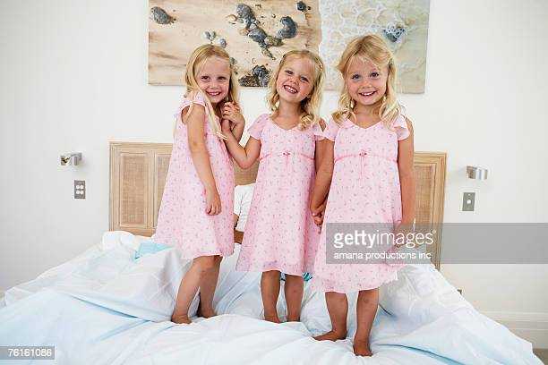 Triplets standing on bed (portrait)