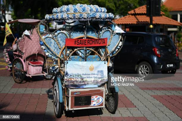 A trishaw is seen with a banner reading 'Save Rohingya' in Malaysia's historical city of Malacca on October 6 2017 The Portuguese arrived in the...