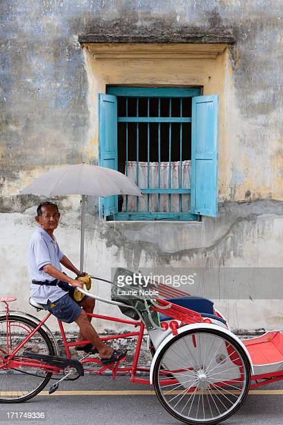 Trishaw under colourful window shutters