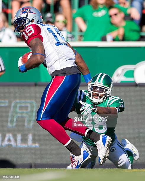 Tristan Jackson of the Saskatchewan Roughriders reaches to try and tackle SJ Green of the Montreal Alouettes in the game between the Montreal...