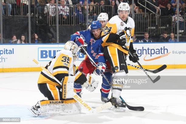 Tristan Jarry of the Pittsburgh Penguins makes a save as Oscar Lindberg of the New York Rangers battles for the rebound at Madison Square Garden on...