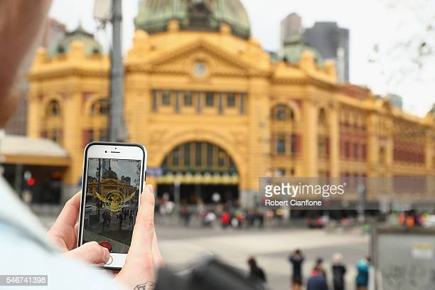 Tristan plays the Pokemon Go game on his phone in front of Flinders Stret Station on July 13 2016 in Melbourne Australia The augmented reality app...