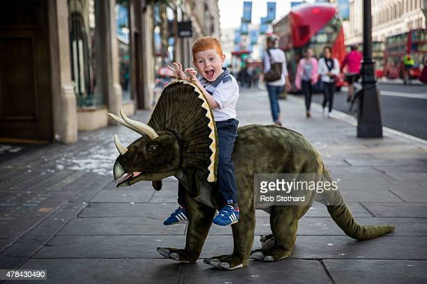 Tristan plays with a toy Triceratops outside Hamleys on Regent Street on June 25 2015 in London England The dinosaur which is 1m30cm in length sells...