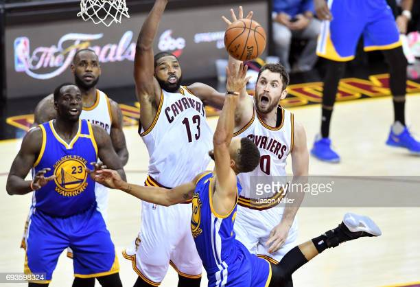 Tristan Thompson and Kevin Love of the Cleveland Cavaliers defend Stephen Curry of the Golden State Warriors in the first half in Game 3 of the 2017...